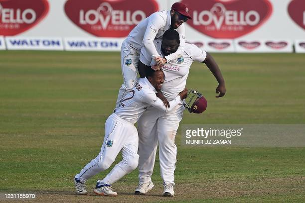 West Indies' John Campbell with teammates Rahkeem Cornwall and Shayne Moseley celebrate the dismissal of Bangladesh's Liton Das during the fourth day...