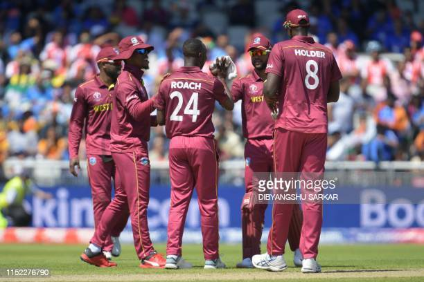 West Indies' Kemar Roach celebrates with teammates the wicket of India's Kedar Jadhav for 7 during the 2019 Cricket World Cup group stage match...