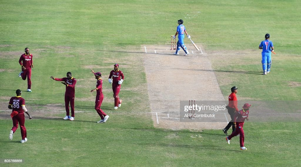 West Indies' Kesrick Williams (L-C) celebrates after dismissing India's MS Dhoni (#7) during the fourth One Day International (ODI) match between West Indies and India at the Sir Vivian Richards Cricket Ground in St. John's, Antigua, on July 2, 2107. West Indies defeated India by 11 runs as the visitor lead the five-match-ODI-series 2-1. / AFP PHOTO / Jewel SAMAD