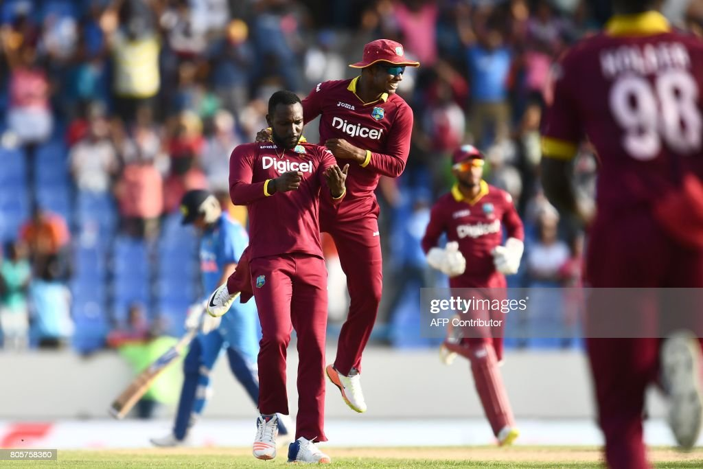 West Indies' Kesrick Williams (L) celebrates with teammates after dismissing India's MS Dhoni (back) during the fourth One Day International (ODI) match between West Indies and India at the Sir Vivian Richards Cricket Ground in St. John's, Antigua, on July 2, 2107. West Indies defeated India by 11 runs as the visitor lead the five-match-ODI-series 2-1. / AFP PHOTO / Jewel SAMAD