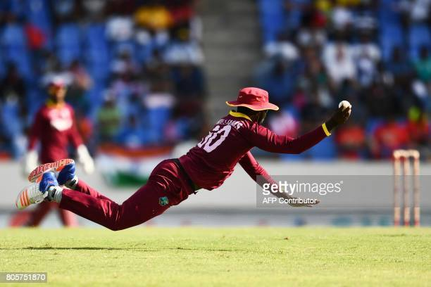 West Indies' Kesrick Williams dives to field the ball during the fourth One Day International match between West Indies and India at the Sir Vivian...
