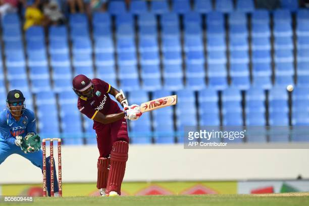 West Indies' Kyle Hope plays a shot as India's wicketkeeper MS Dhoni looks on during the fourth One Day International match between West Indies and...