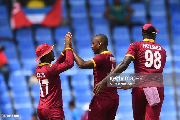 West Indies' Miguel Cummins celebrates with teammate Evin Lewis and captain Jason Holder after dismissing India's Shikhar Dhawan during the third One...