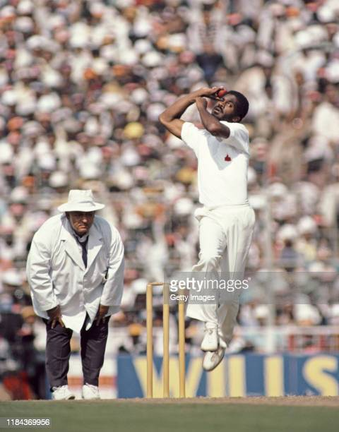 West Indies pace bowler Michael Holding in action as umpire Swaroop Kishen looks on during a Test Match against India in December 1983 in India