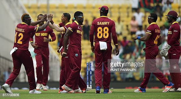 West Indies players celebrate after the wicket of Afghanistan batsman Usman Ghani during the World T20 cricket tournament match between West Indies...