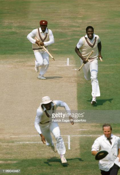 West Indies players Gordon Greenidge Joel Garner and Roger Harper sprint from the field after West Indies win the 5th Test match between England and...