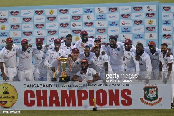 West Indies' players pose with the Test tournament trophy after winning the second Test cricket match against Bangladesh at the Sher-e-Bangla...