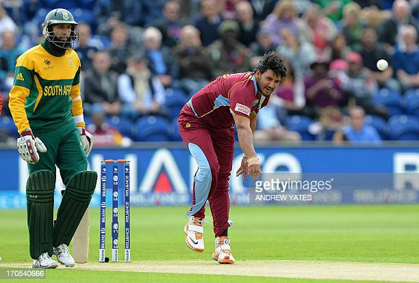 West Indies Ravi Rampaul bowls past South Africa's Hashim Amla during the 2013 ICC Champions Trophy One Day International cricket match between West...