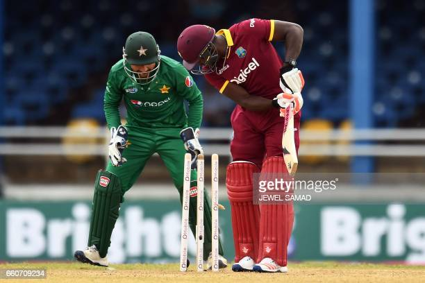 West Indies' Rovman Powell is clean bowled off Pakistan's Shadab Khan as his team captain/wicketkeeper Sarfraz Ahmed celebrates during the second of...