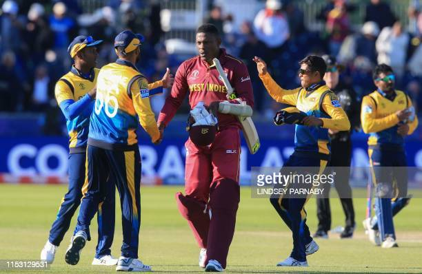 West Indies' Sheldon Cottrell shakes hands with Sri Lanka's players as they walk off the field after victory in the 2019 Cricket World Cup group...