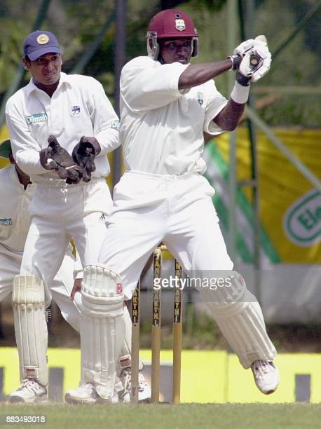 West Indies skipper Carl Hooper bats for four as Sri lankan wicketkeeper Kumar Sangakkara looks on during the fourth day of the second cricket test...