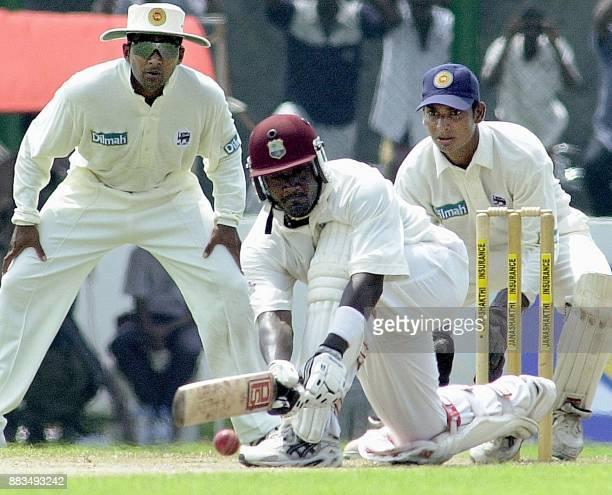 West Indies skipper Carl Hooper sweeps a ball as Sri Lankan fielder Mahela Jayawardena and wicketkeeper Kumar Sangakkara looks on during the Second...