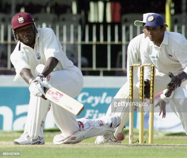 West indies skipper Carl Hooper sweeps a ball to the boundry for four as Sri Lanka wicket keeper Kumar Sangakkara looks on during the First day of...