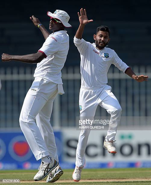 West Indies' spinner Devendra Bishoo celebrates with team captain Jason Holder after taking the wicket of Pakistani batsman Mohammad Nawaz unseen on...