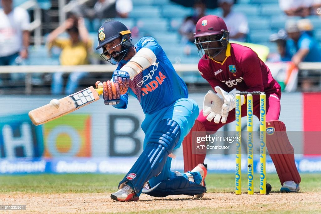 West Indies' wicketkeeper Chadwick Walton (R) fields as India's Dinesh Karthik plays a shot during the T20 match between West Indies and India at the Sabina Park Cricket Ground in Kingston, Jamaica, on July 9, 2017. /