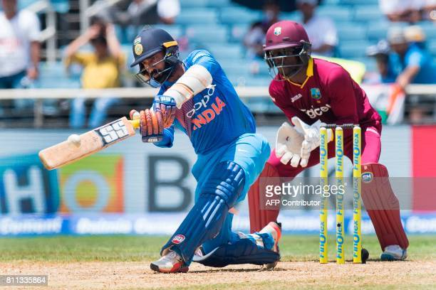 West Indies' wicketkeeper Chadwick Walton fields as India's Dinesh Karthik plays a shot during the T20 match between West Indies and India at the...