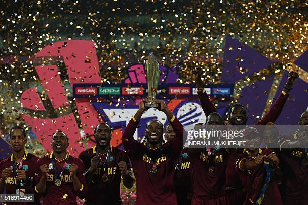 West Indies's captain Darren Sammylooks on as teammates including Chris Gaylecelebrate with the trophy after victory in the World T20 cricket...