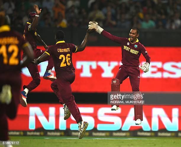 West Indies's Carlos Brathwaite celebrates with teammate Denesh Ramdin and captain Darren Sammyafter the dismissal of England's Joe Root during the...