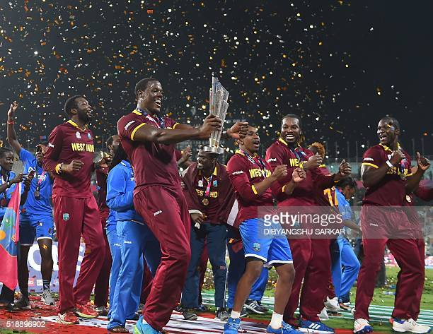 West Indies's Carlos Brathwaite holds the trophy as he celebrates after winning the World T20 cricket tournament final match between England and West...