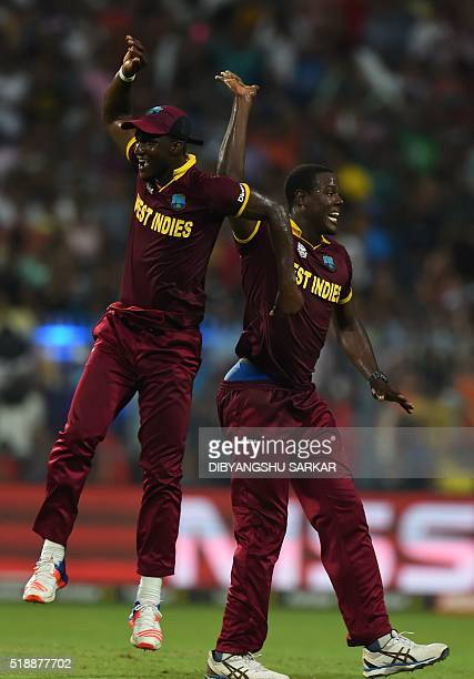 West Indies's Carlos Brathwaitecelebrates with captain Darren Sammy after the wicket of England's Jos Buttler during the World T20 cricket tournament...