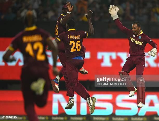 West Indies's Carlos Brathwaitecelebrates with teammate Denesh Ramdinand captain Darren Sammyafter the dismissal of England's Joe Root during the...