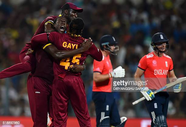 West Indies's Carlos Brathwaitecelebrates with teammates Darren Sammy and Chris Gayle after the wicket of England's Jos Buttler during the World T20...