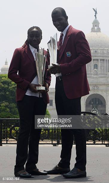 West Indies's cricket captains Stafanie Taylor and Darren Sammy pose for a photograph with the World T20 cricket tournament trophy one day after West...