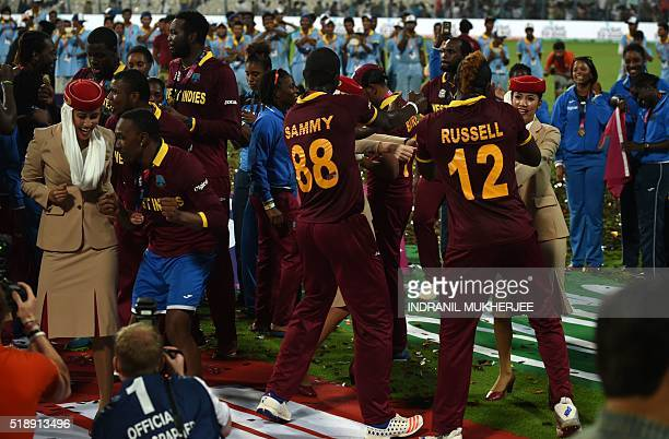 West Indies's Dwayne Bravocaptain Darren Sammyand teammate Andre Russelldance with air hostesses after victory in the World T20 cricket tournament...