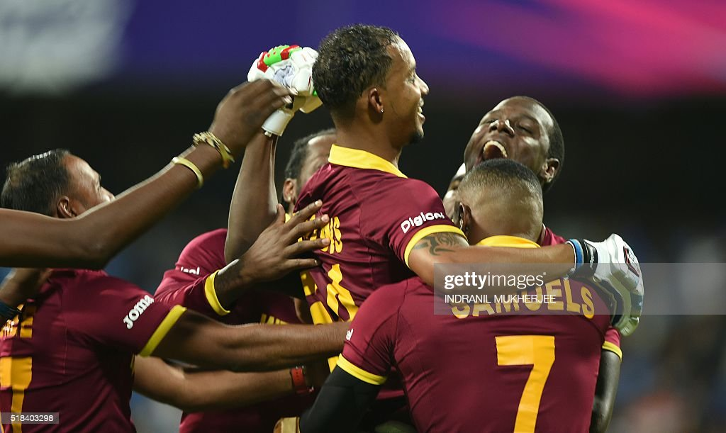 West Indies's Lendl Simmons(C)is held aloft by teammates as they celebrate after victory in the World T20 cricket tournament second semi-final match between India and West Indies at The Wankhede Stadium in Mumbai on March 31, 2016. / AFP / INDRANIL