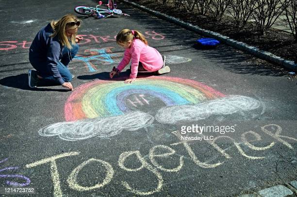 Eight year old Anna Weir and her mother Melissa Weir make chalk drawings on the driveway of their West IslipNew York home to help brighten the mood...