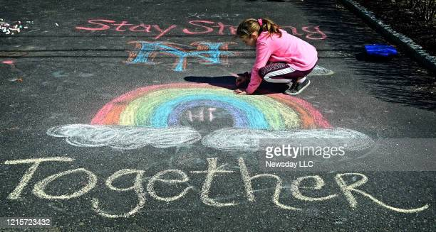 Girl makes chalk drawings on the driveway of their West Islip New York home to help brighten the mood of people passing by while everyone is under...