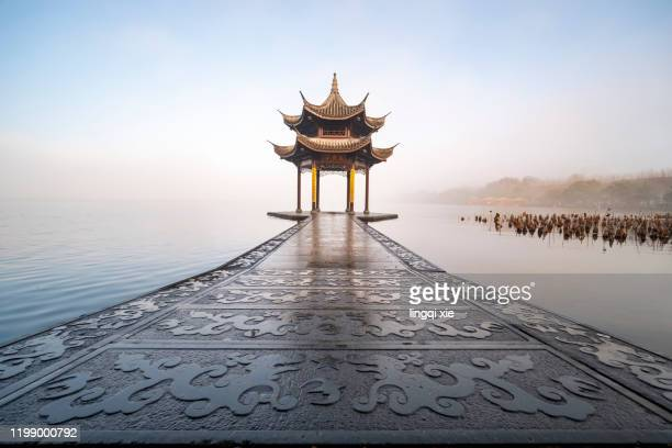 west lake in hangzhou, china in the fog - west lake hangzhou stock pictures, royalty-free photos & images