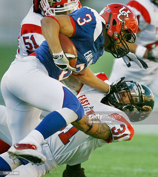 West Team wide receiver Anthony Parker runs over East Team free safety Brian Lainhart during the EastWest Shrine Game at the Florida Citrus Bowl in...