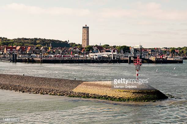 west terschelling town and pier seen from the water, with brandaris lighthouse rising above. - merten snijders - fotografias e filmes do acervo