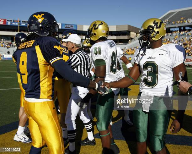 West Virginia and South Florida captains shake hands just before the coin toss in Saturday's game at Milan Puskar Stadium at Mountaineer Field in...