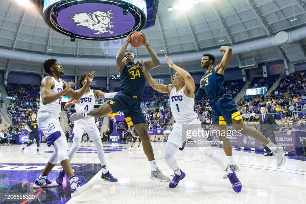 West Virginia Mountaineers forward Oscar Tshiebwe grabs a rebound over TCU Horned Frogs guard Desmond Bane and TCU Horned Frogs center Kevin Samuel...