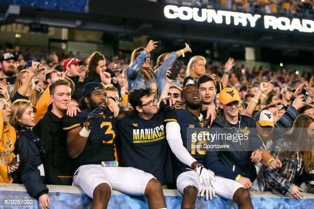 West Virginia Mountaineers linebacker AlRasheed Benton and West Virginia Mountaineers safety Marvin Gross Jr jump into the student section and join...