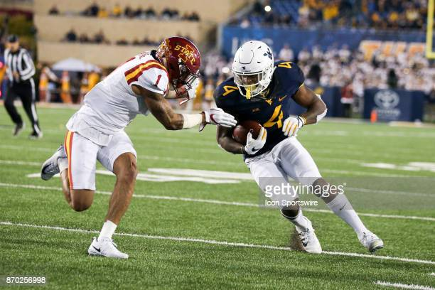 West Virginia Mountaineers running back Kennedy McKoy rushes for a first down to help run out the clock as Iowa State Cyclones defensive back D'Andre...