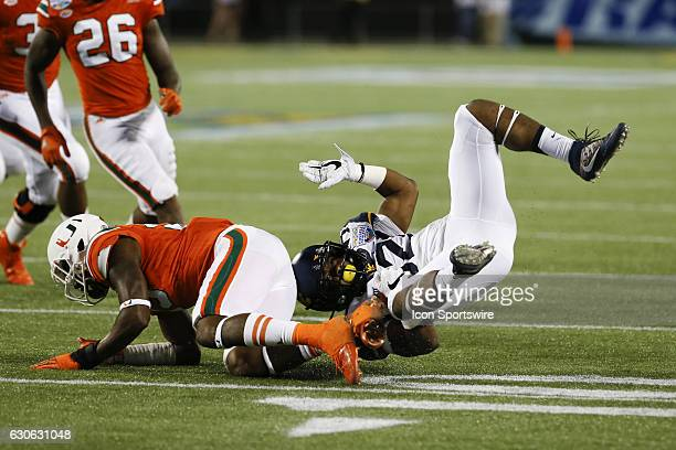 West Virginia Mountaineers running back Martell Pettaway is flips after being hit by Miami Hurricanes defensive back Adrian Colbert in the 4th...