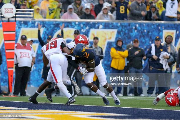 West Virginia Mountaineers wide receiver Gary Jennings Jr powers thru the tackle attempt of Youngstown State Penguins cornerback Chrispin Lee and...