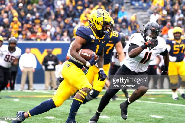 West Virginia Mountaineers Wide Receiver TJ Simmons runs with the ball after making a catch with Oklahoma State Cowboys Linebacker Amen Ogbongbemiga...