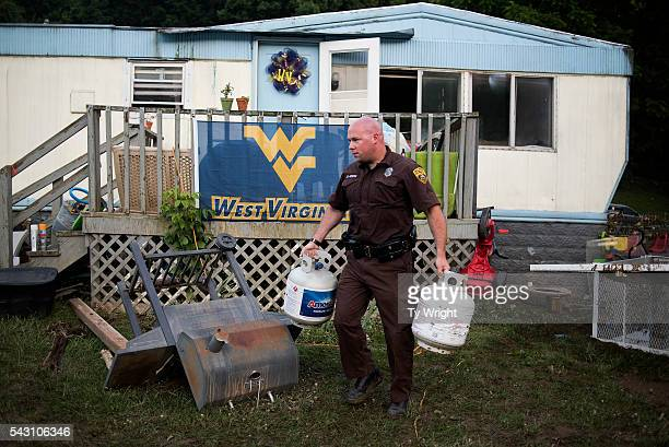 West Virginia Natural Resources Police Officer carries propane tanks he and other officers found washed up in the front yard of a home after the...