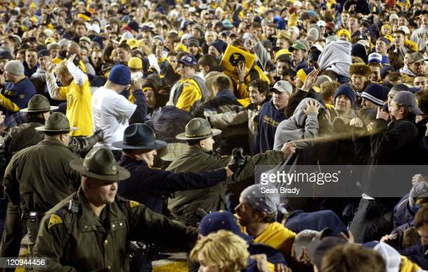 West Virginia State Police react to the crowds taunts and aggessiveness to reach the goal post following West Virginia's upset of undefeated Virginia...