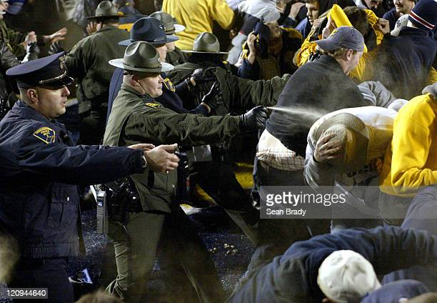 West Virginia University students and fans continue to surge forward toward the goalpost despite the onslaught of pepper spray from West Virginia...