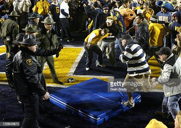 West Virginia University students and fans struggle for a large padding to help protect themselves against the pepper spray from West Virginia State...