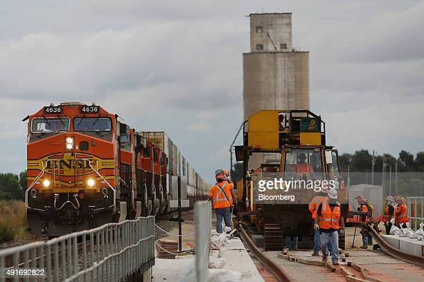 A Westbound intermodal train passes by maintenanceofway workers using a track laying machine to construct a second main line on the Burlington...
