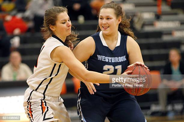 Westbrook senior Julia Symbol flashes a grin as Biddeford sophomore Hailey Allen swats the ball away