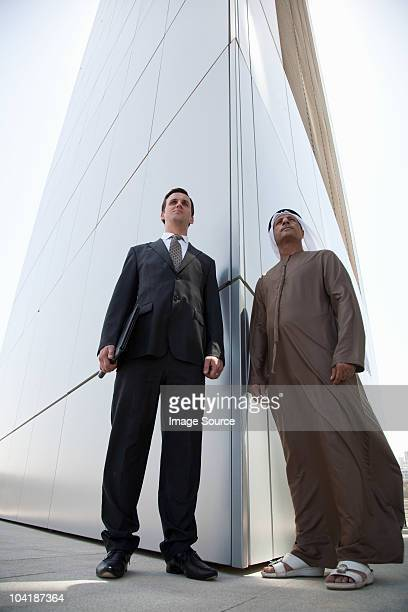 western and middle eastern businessmen outside modern building - low angle view stock pictures, royalty-free photos & images