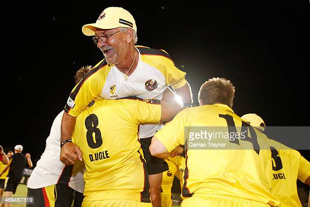 Western Australian team manager Ash Taylor embraces his players after their win in the Imparja Cup Final between Western Australia and New South...