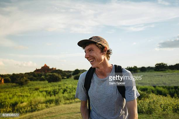 western backpacker smiling outdoors with temple in the background, south east asia. - rucksacktourist stock-fotos und bilder